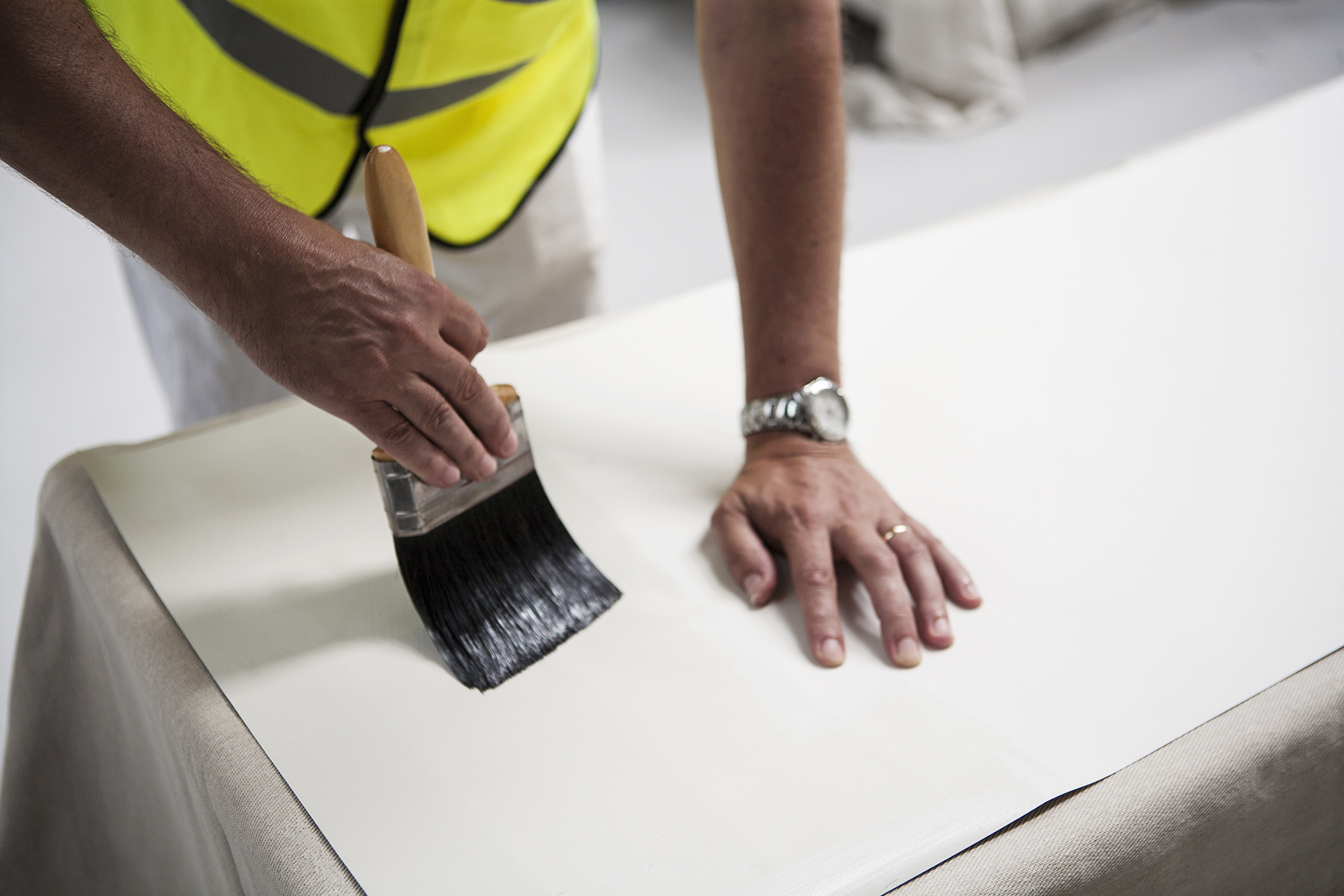 Editorial photography for business by Stephen Cole, commercial photographer based in Rochester. In this image, a painter and decorator applies paste to a length of wallpaper.