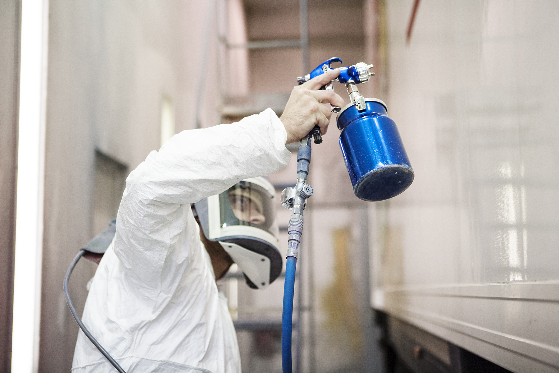 Editorial photography for business by Stephen Cole, commercial photographer based in Rochester. In this image, a man wearing a full-face mask and overalls sprays paint on to a lorry.